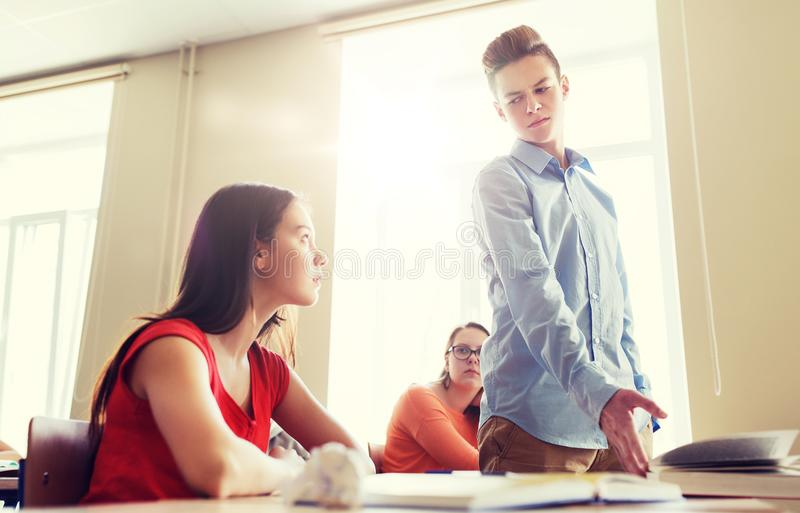 Students gossiping behind classmate back at school. Education, bullying, conflict, social relations and people concept - student boy behaving unfriendly to girl stock images