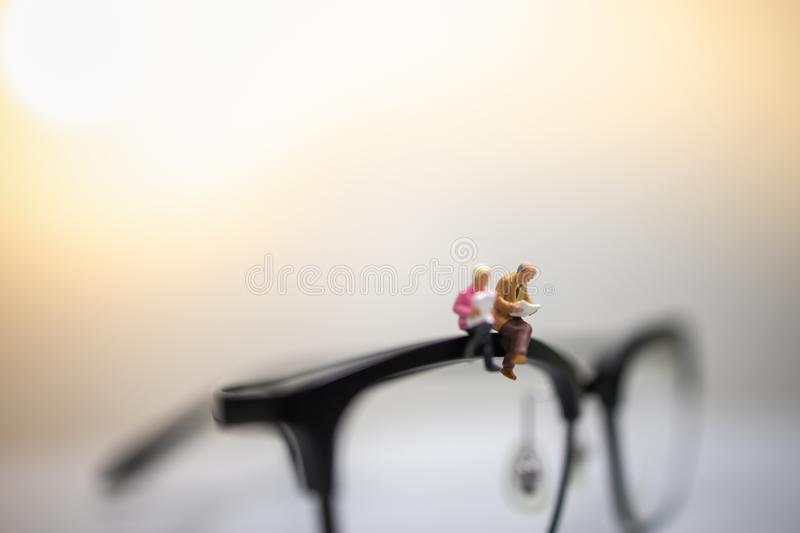 Education and Business Concept. Close up of businessman miniature figures sitting and reading book on reading glasses with copy stock images