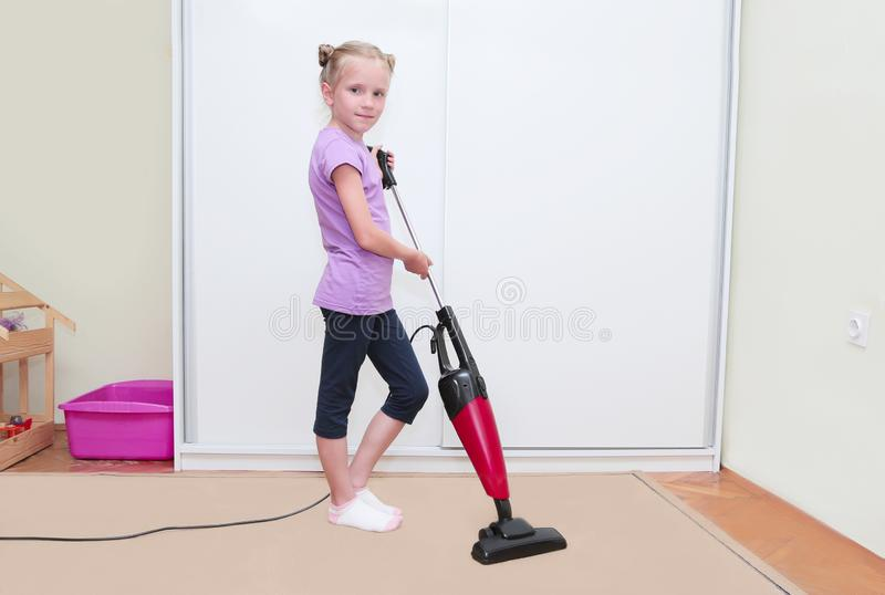 Education of children concept, cleaning. Young blond girl cleaning carpet in her room with vacuum cleaner royalty free stock photo