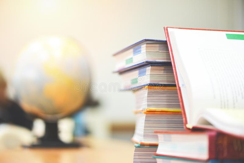 Education concept back to school and business study global world - open book in library with book stacked and earth globe model stock photos