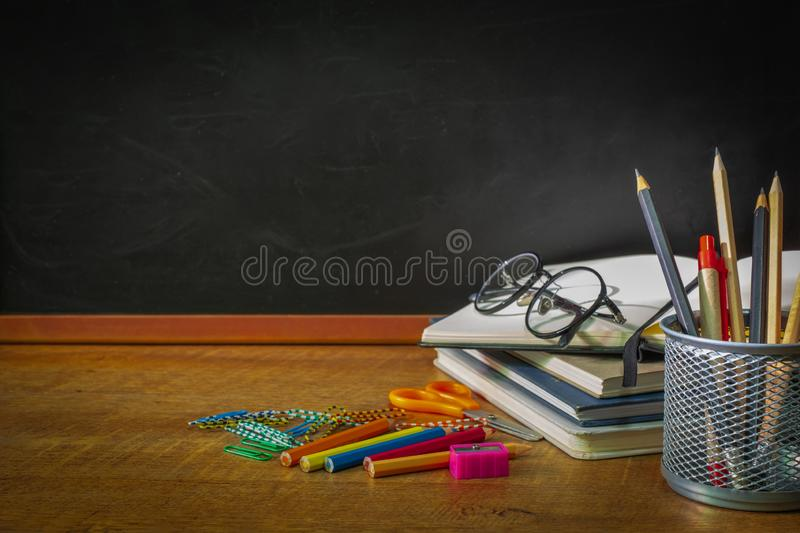 Education, Concept Back To School. front view of School Supplies  chalkboard on wooden table  with  books, glasses, color, Pencil, royalty free stock photo