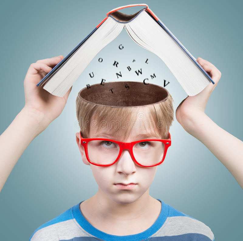 Education concept. Boy looking at camera with a book and letters under his opened head royalty free stock images
