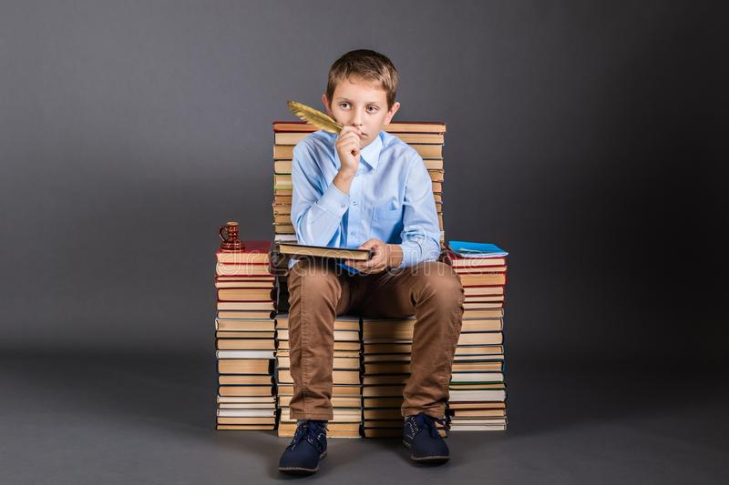 Education concept. A boy with quill pen sits on a throne stock images