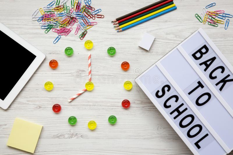 Education concept. Eight hours on watch. Clock made of colorful candies, `back to school` word on modern board, accessories for. Study over white wooden royalty free stock photography