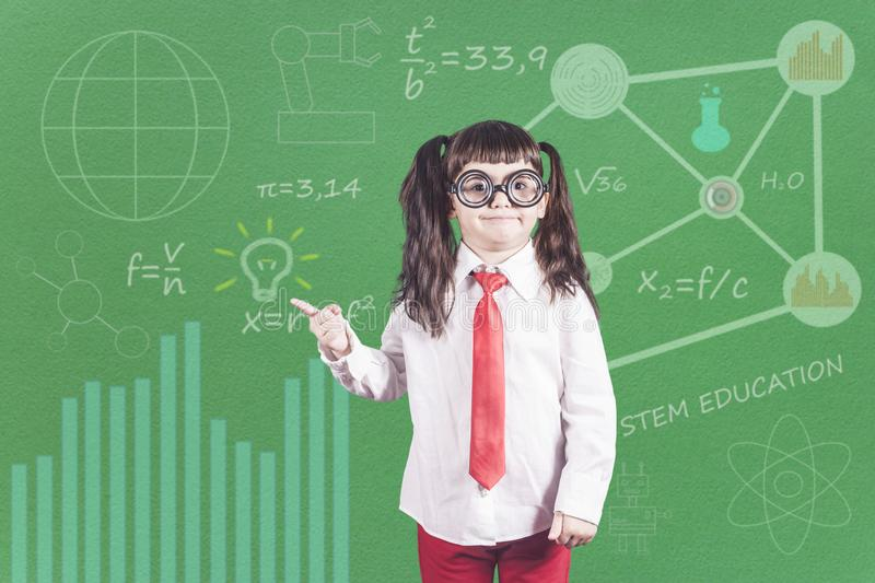 Education concept. Funny little genius school girl in front of a chalkboard royalty free stock images