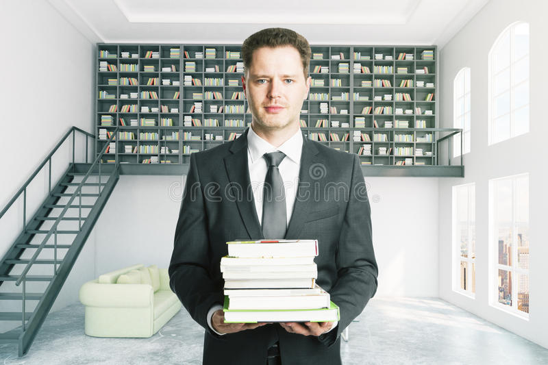 Education concept. Handsome businessman with pile of books in modern library interior. Education concept stock photo