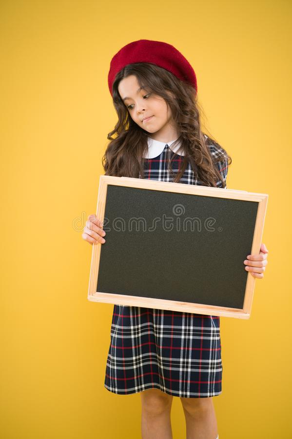 Education concept. happy girl in french beret. advertising board for promotion. school shopping sales. child on yellow royalty free stock photo