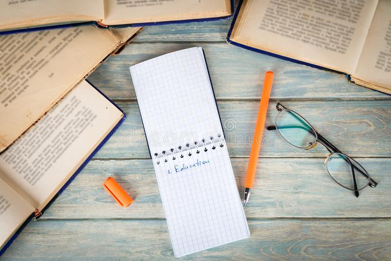Education concept. Opened notebook among old books stock photography