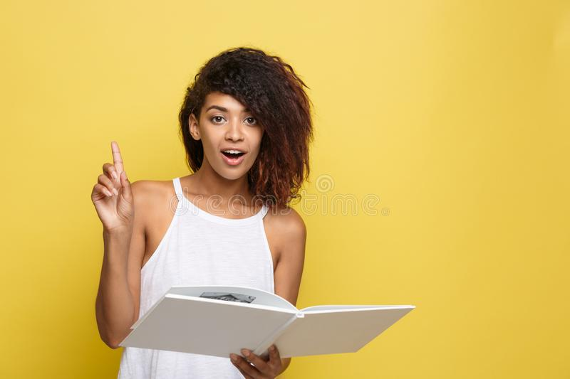 Education Concept - Portrait of African American woman reading a book and get some ideas. Yellow studio background. Copy. Space royalty free stock images