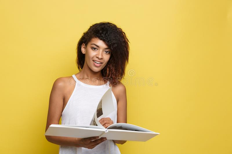 Education Concept - Portrait of African American woman reading a book. Yellow studio background. Copy Space. Education Concept - Portrait of African American royalty free stock images