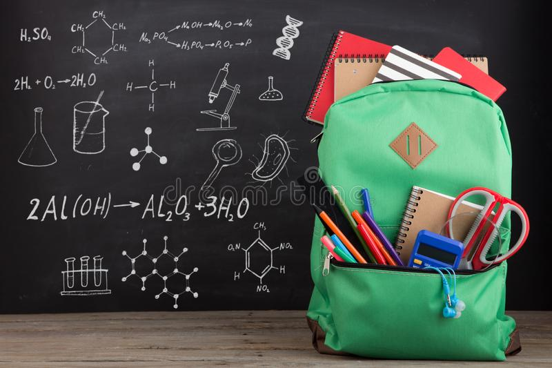 Education concept - school backpack with books and other supplies, blackboard background stock images