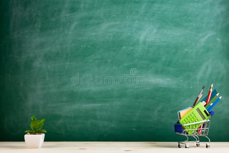 Education concept - school supplies in a shopping cart on the desk in the auditorium, blackboard background stock images