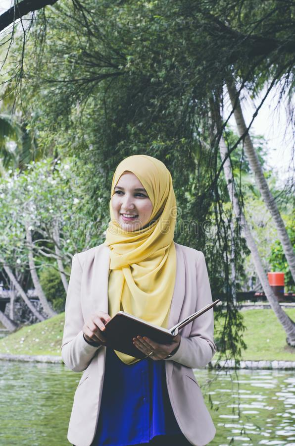 Smile face young muslimah woman standing and holding notebooks in park. stock photos