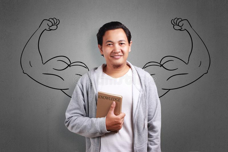 Education Concept Strong With Knowledge. Education concept power with knowledge. Young Asian man holding book and smiling with strong big arms drawing behind stock images