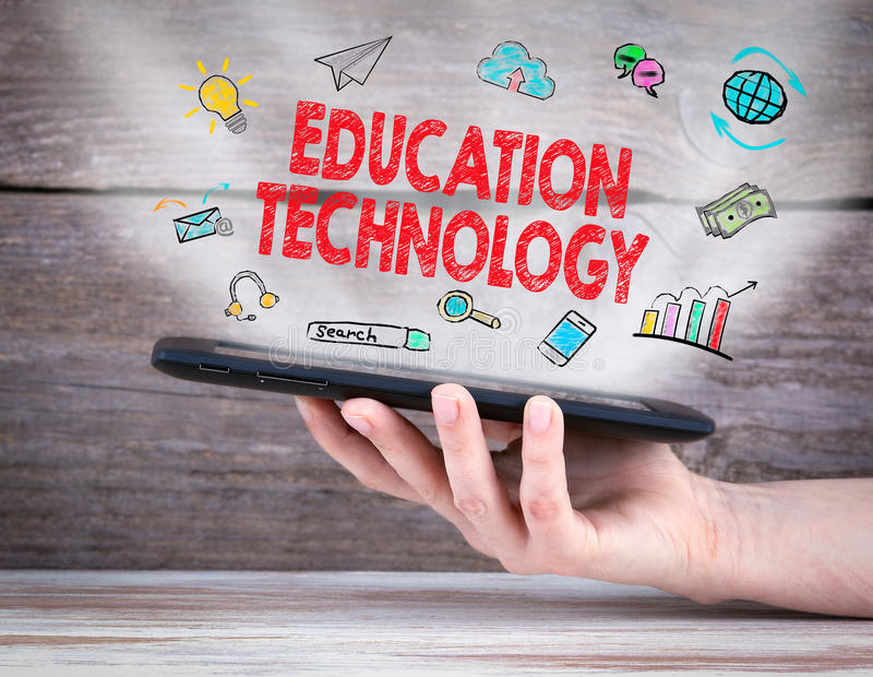 Education concept. Tablet computer in the hand. Old wooden background stock photography