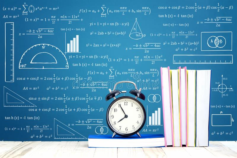 Education Concept. Text Books and alarm clock on the wooden pallet table with mathematics formula background royalty free stock photo