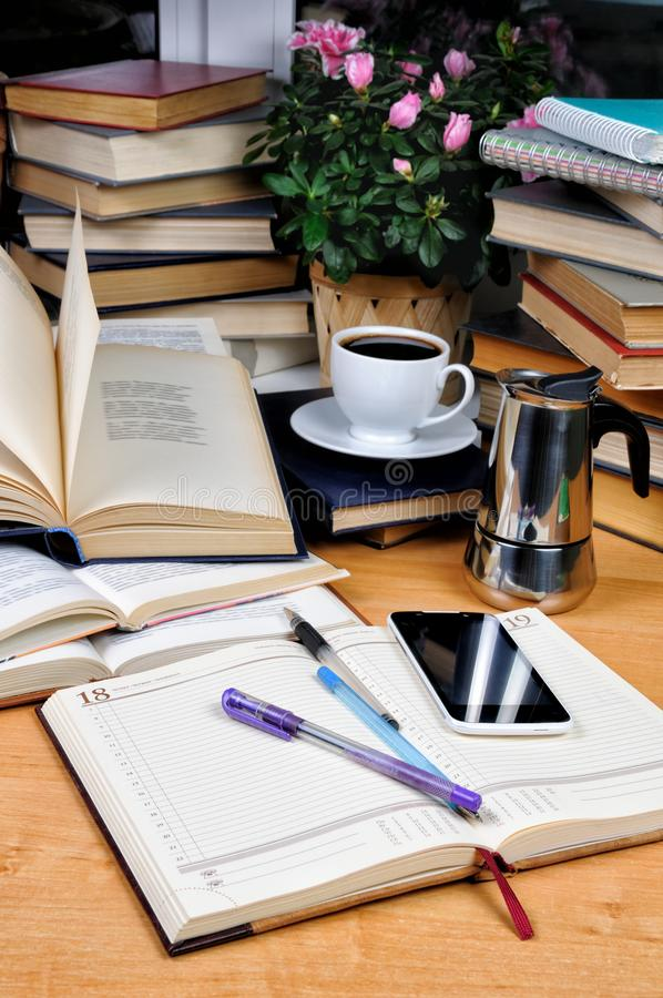 Education concept. Textbooks, notepad and pen with a cup of black coffee with a coffee pot on a wooden table. Education concept stock images