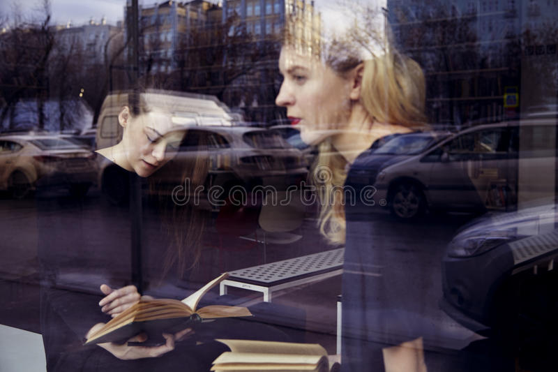 Education concept. Two blonde girls are sitting near window in a library royalty free stock photography