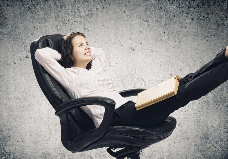 Education concept. Young businesswoman sitting in chair and reading book royalty free stock photography