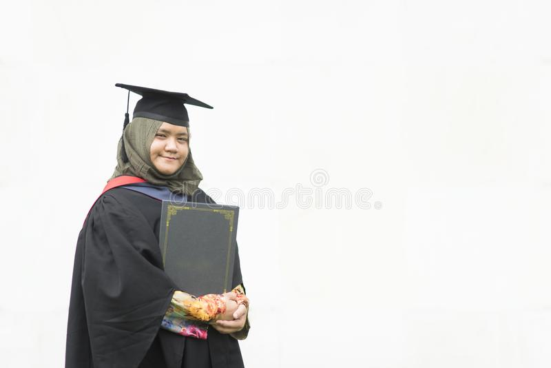 Young Malaysian woman holding a degree certificate while smiling on her graduation day isolated on white background royalty free stock photography