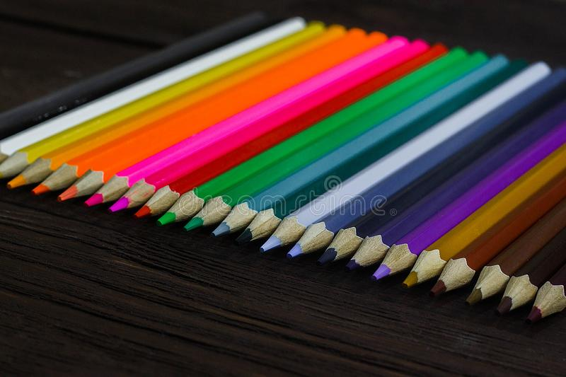 Education and creativity concept: colored pencils on wooden background.  stock photos