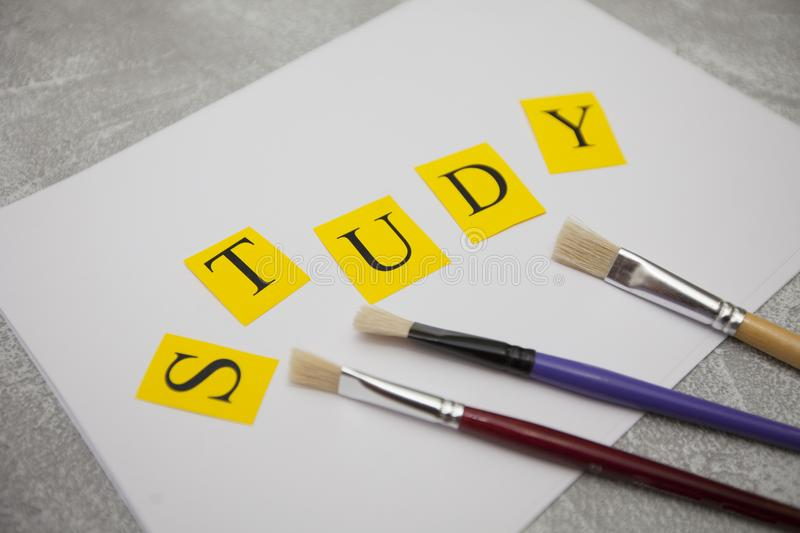 Education and creativity concept. Education Creativity concept. A paper sheet, paint brushes and STUDY inscription on a light stone background, close up royalty free stock photography