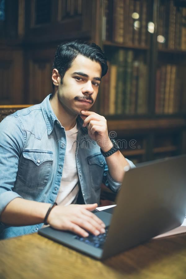 Education in Europe. Arabic young man working with computre in old library royalty free stock photos