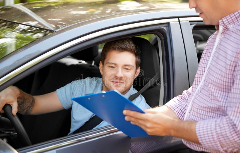 Car driving instructor with clipboard and driver. Education, examination and people concept - driving school instructor with clipboard and male driver in car royalty free stock images
