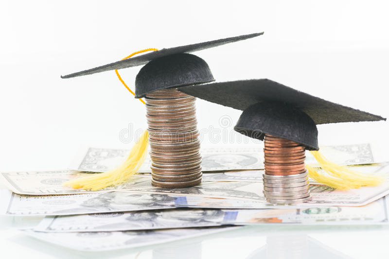 Education Funds. Mortarboards and stacked of coins on top of US dollar banknotes close up royalty free stock photography