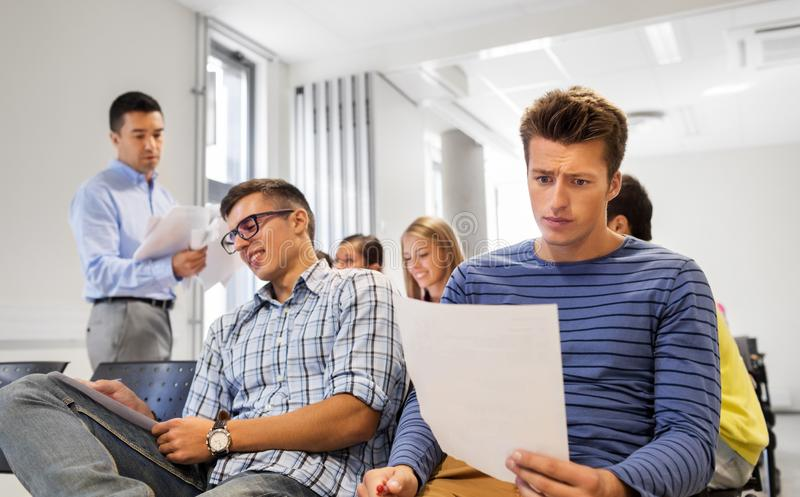 Students with tests and teacher at lecture hall stock images