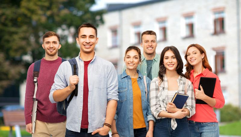 Group of smiling students with books over campus. Education, high school and people concept - group of smiling students with books over campus background royalty free stock photography