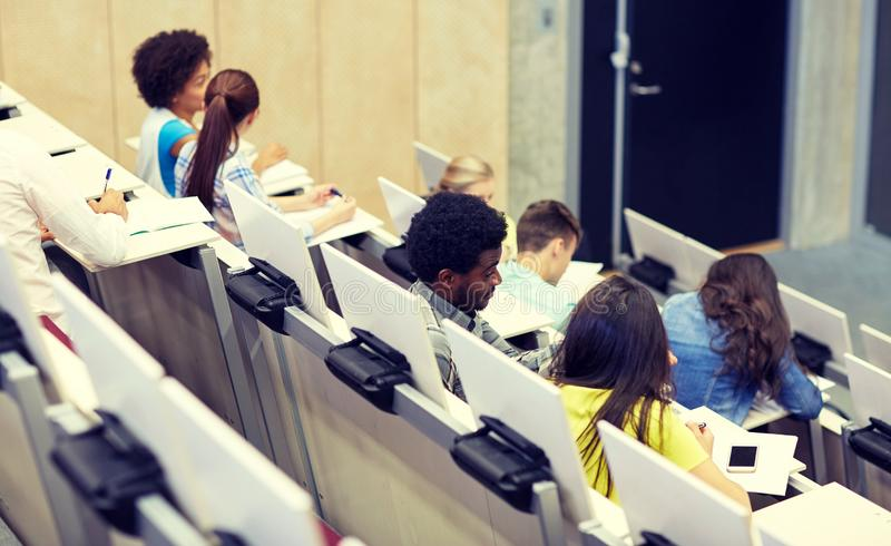 International students at university lecture hall. Education, high school, university, learning and people concept - group of international students talking in stock photography