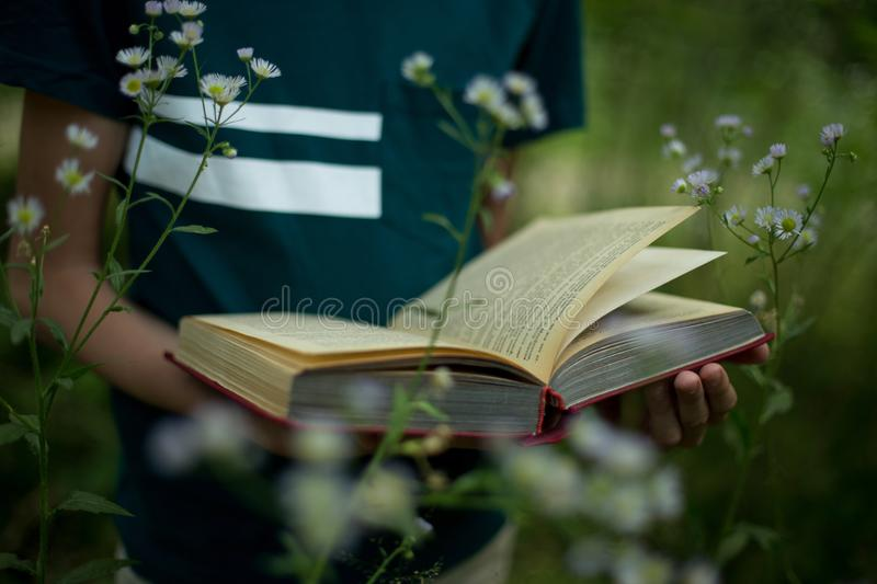 Education concept - teenager is holding a book in his hands in nature royalty free stock photos