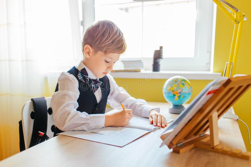 Education at home concept - Cute little boy studying or completing home work on study table with pile of books, educational globe. And workbook royalty free stock images