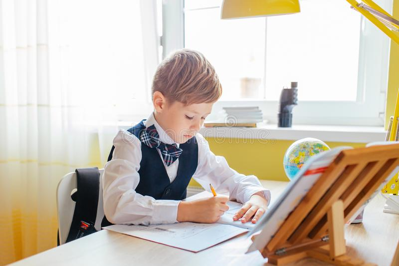 Education at home concept - Cute little boy studying or completing home work on study table with pile of books, educational globe. And workbook royalty free stock photography