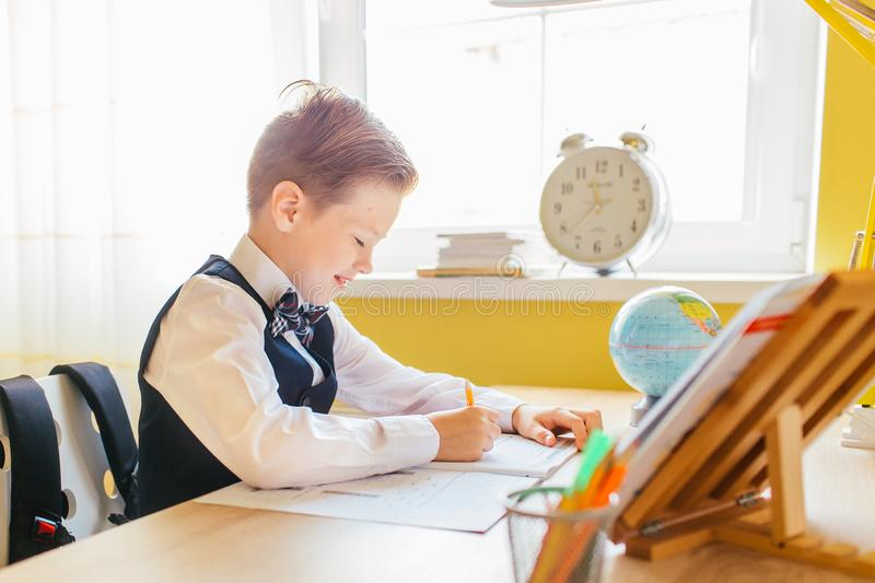 Education at home concept - Cute little boy studying or completing home work on study table with pile of books, educational globe. And workbook stock photography