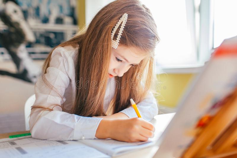 Education at home concept - Cute little girl with long hair studying or completing home work on a table with pile of books and. Workbook royalty free stock photography