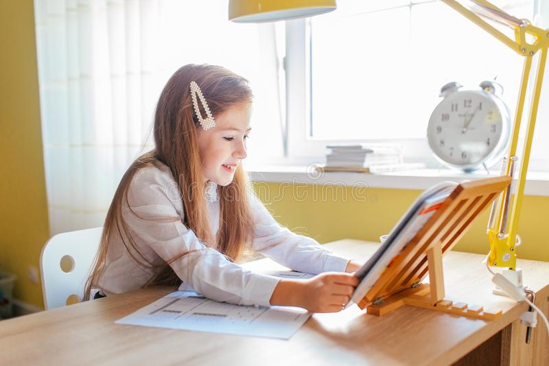Education at home concept - Cute little girl with long hair studying or completing home work on a table with pile of books and. Workbook stock photography