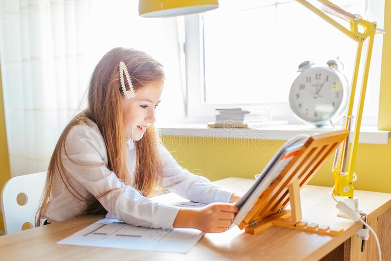 Education at home concept - Cute little girl with long hair studying or completing home work on a table with pile of books and. Workbook stock images