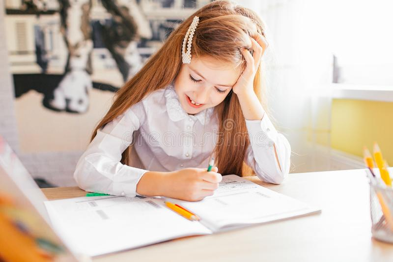 Education at home concept - Cute little girl with long hair studying or completing home work on a table with pile of books and. Workbook stock photo