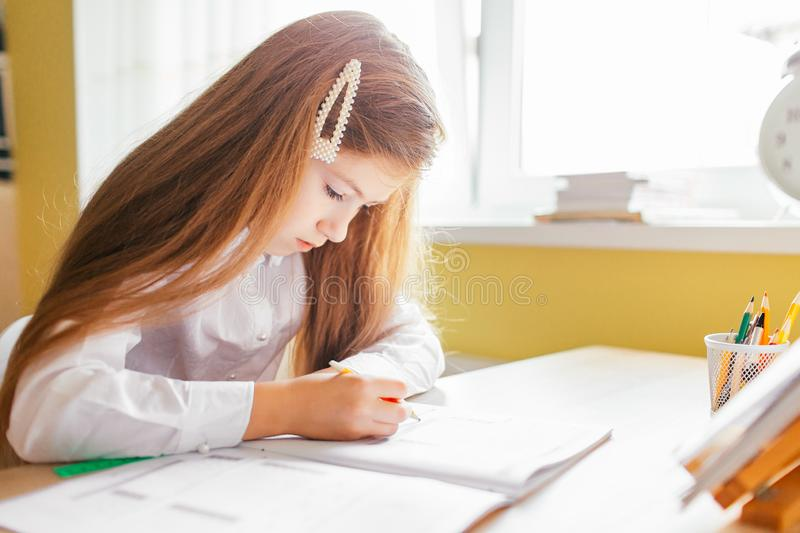 Education at home concept - Cute little girl with long hair studying or completing home work on a table with pile of books and. Workbook stock photos