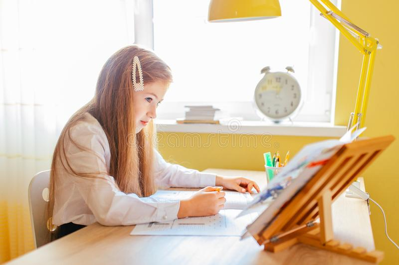 Education at home concept - Cute little girl with long hair studying or completing home work on a table with pile of books and. Workbook royalty free stock photo