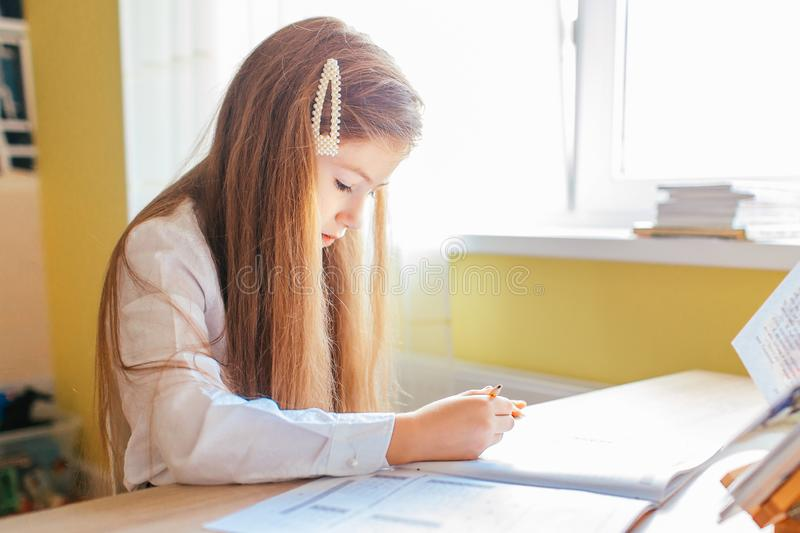Education at home concept - Cute little girl with long hair studying or completing home work on a table with pile of books and. Workbook royalty free stock images