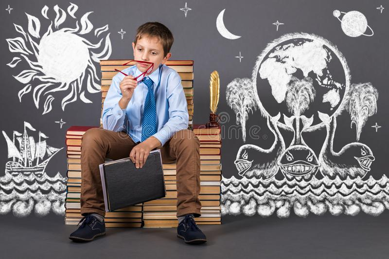 A boy sitting on a throne from books plans his daily routine royalty free stock photography