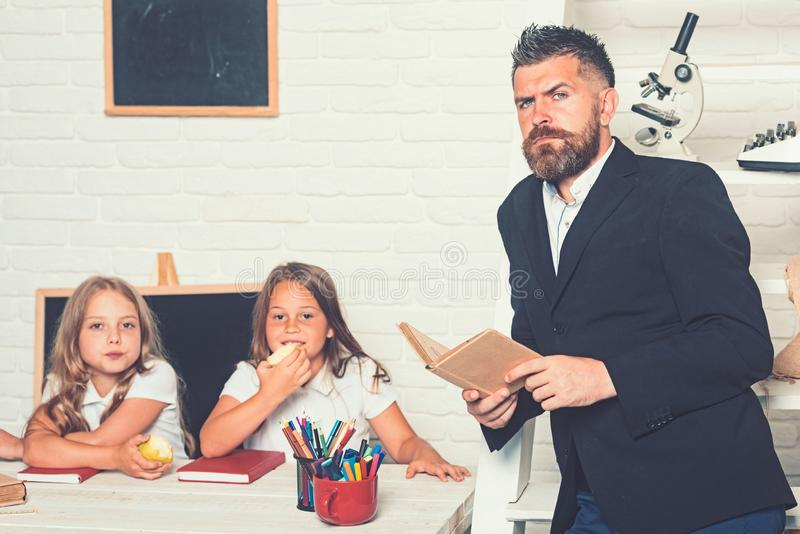 Education in knowledge day. Literature lesson and reading grammar book. School time of sisters and father in library stock photos