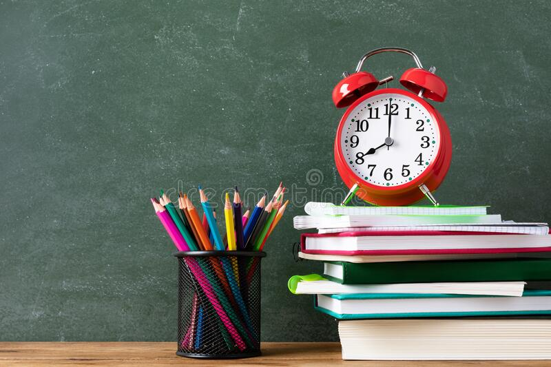 Education and learning background with red alarm clock and paper notebooks with colorful pencils against blackboard.Back to school stock photo