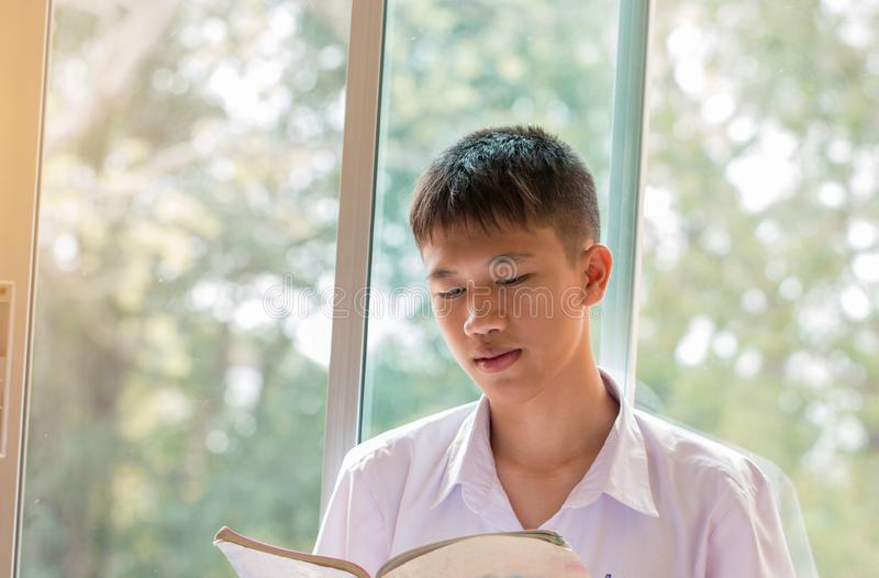 Education learning Concept: Happy Asian young man student reading book and taking note for studying check timetable for projected royalty free stock photos