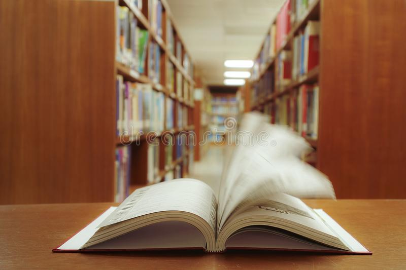Education learning concept with quickly opening book or textbook in old library, and aisle of bookshelves in library university royalty free stock images