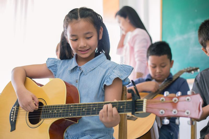 Education music concept. Little cute girl playing guitar and smiling in the music class room royalty free stock photos