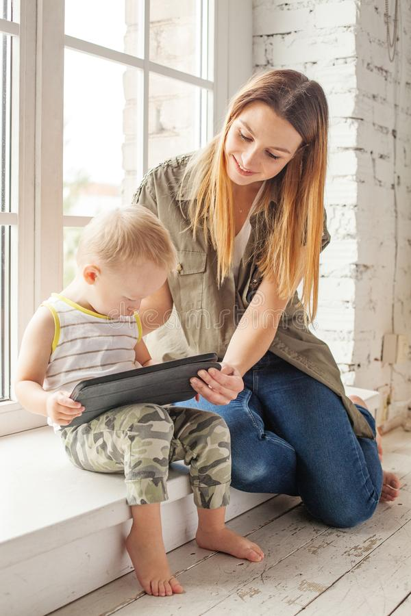 Education and new technology concept. Happy mother with baby using tablet pc computer and learning at home stock photography